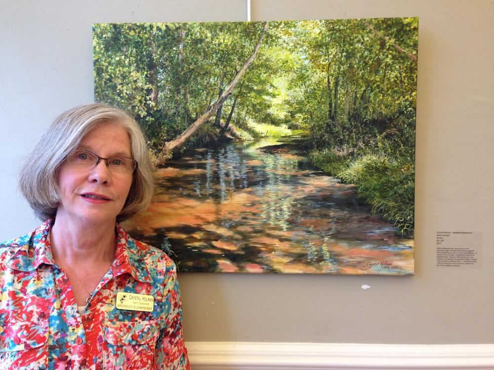Mrs. Crystal Holman standing with a painting